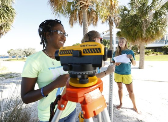 Three female students survey on South Beach with Geoscience and Marine Science Professor Laura Wetzel.