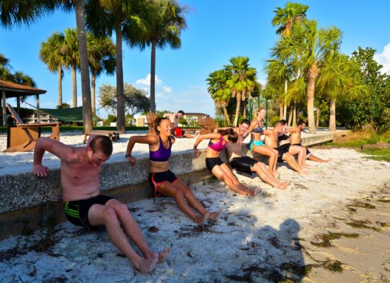 Students do crunches against sea wall for Xfit club on South Beach