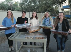 Students holding tubs of food from the campus cafeteria