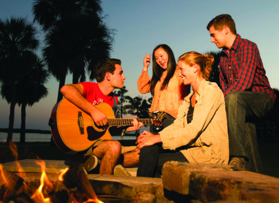 Students laughing and playing guitar at the South Beach fire pit