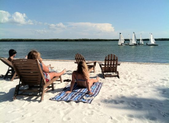 Three students laying on the beach studying while sailboats go by