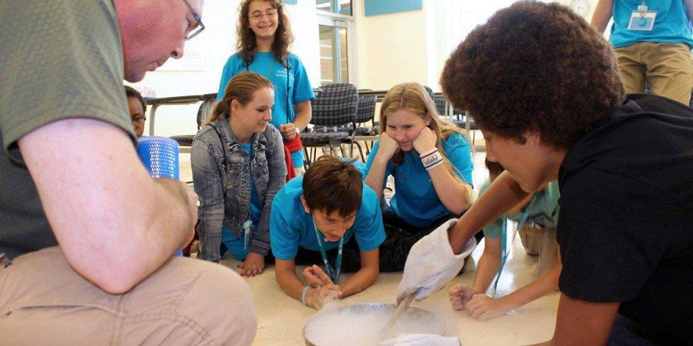 Professor Chris Schnabel helps Summer Science Splash campers make ice cream using liquid nitrogen