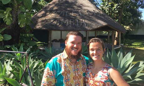 Eckerd College alumni standing in front of hut-like home in Zambia