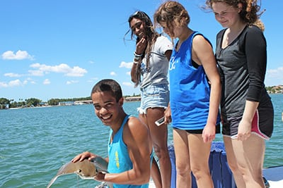 First-year students on a boat, handling a ray