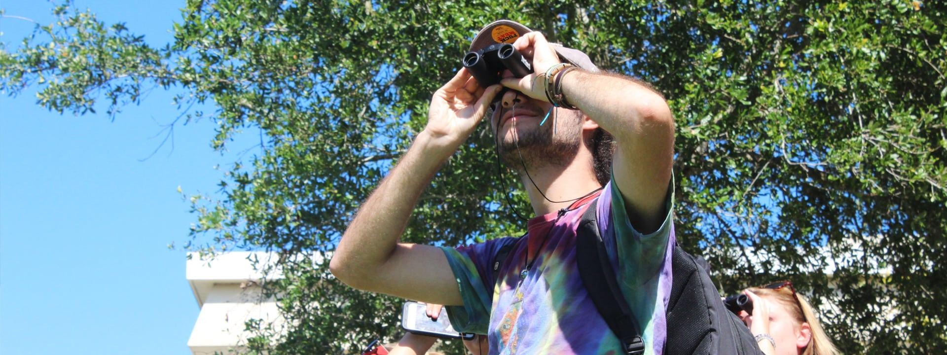 Male student in tie-dye shirt looking through binoculars