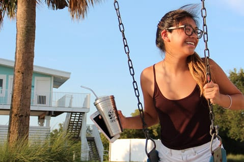 Student swinging while holding reusable beverage container