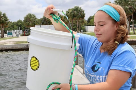 Student holding bucket of sea water off pier