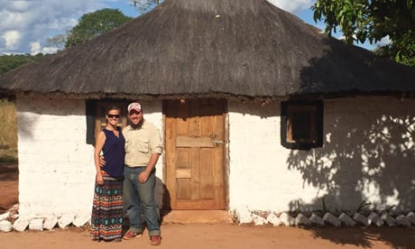 Couple standing in from of simple home in Zambia