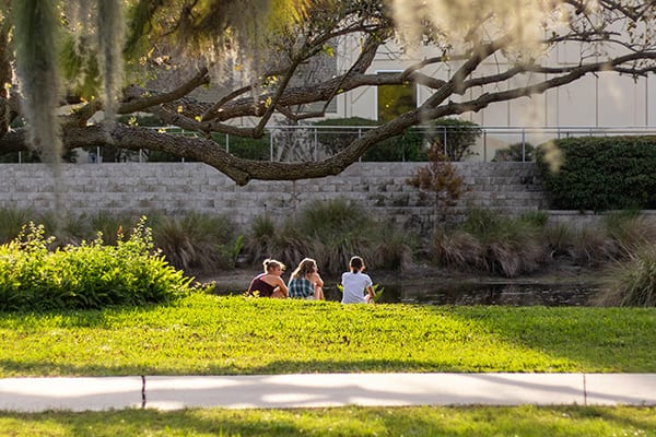 Eckerd students seated along pond by James Center