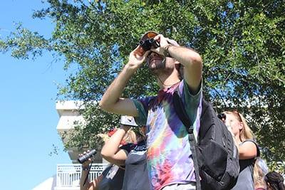 Eckerd birder looking through binoculars