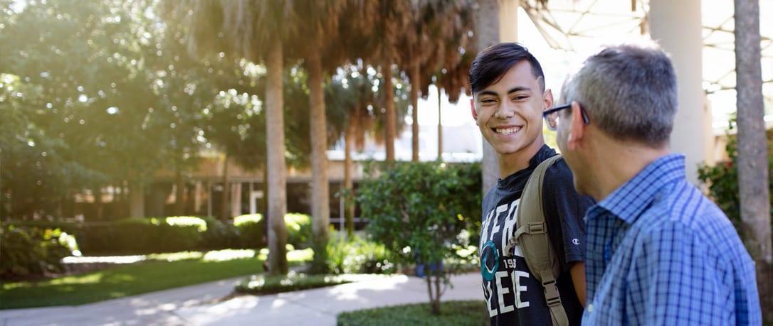 Eckerd College professor walks with student across quad