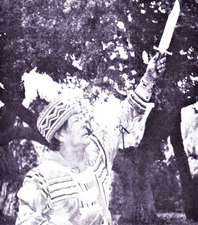 Seminole holding knife in air