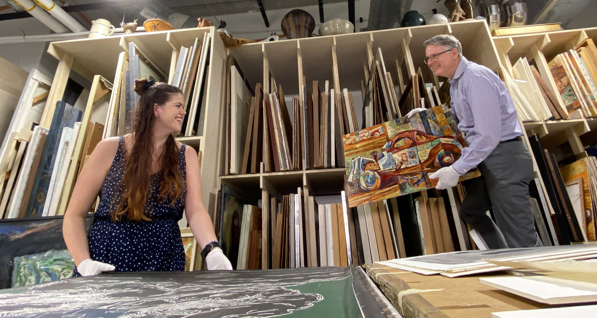 Eckerd art history professor Gliem holds painting for student to see
