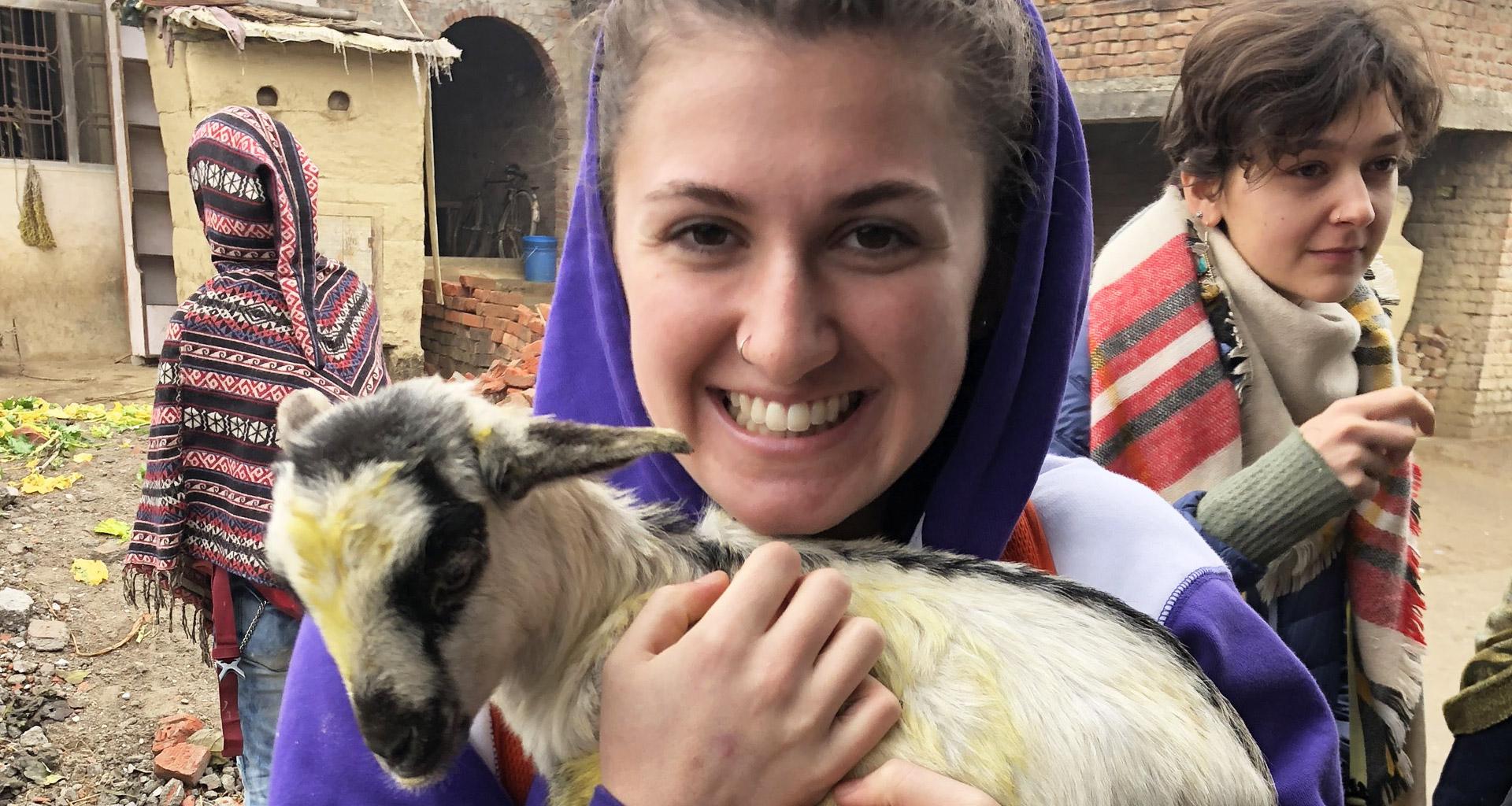 Eckerd student in Nepal holding baby goat